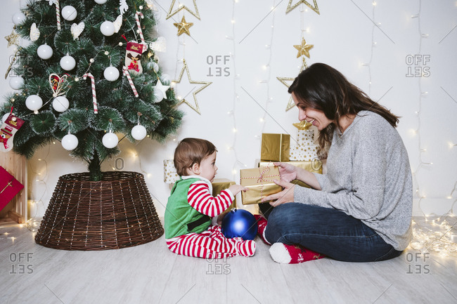 Woman giving gift to baby boy while sitting at home during Christmas