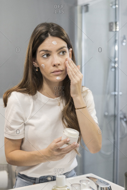 Young woman rubbing cream on face while standing in bathroom at home