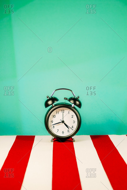 Studio shot of alarm clock standing on white and red striped pattern