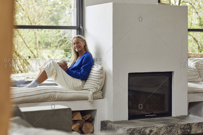 Smiling mature woman with coffee cup sitting on window seat at home