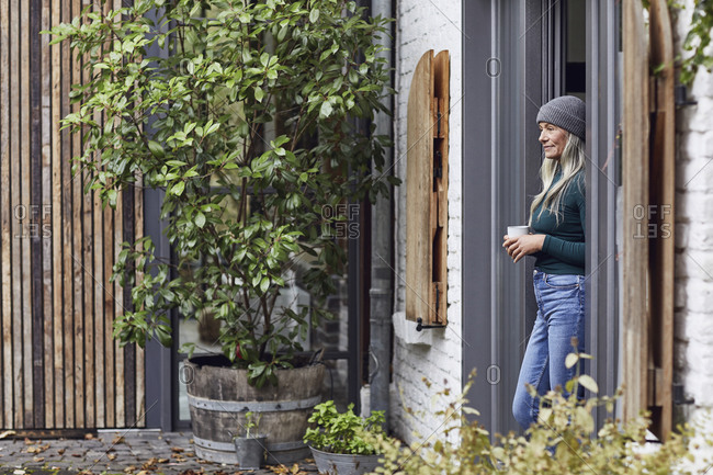 Mature woman holing coffee cup while day dreaming at door of house