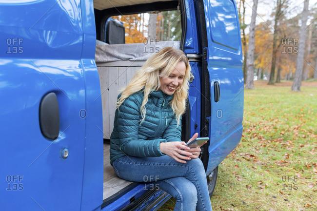 Happy woman using smart phone while siting at door of camper van