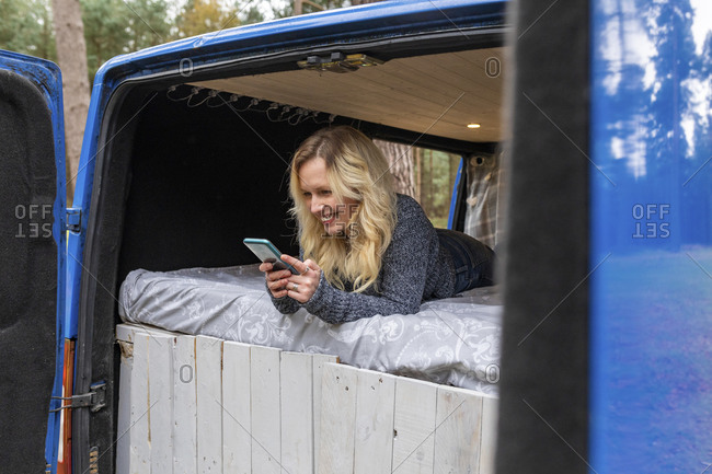 Smiling woman using smart phone while lying on bed in camper van