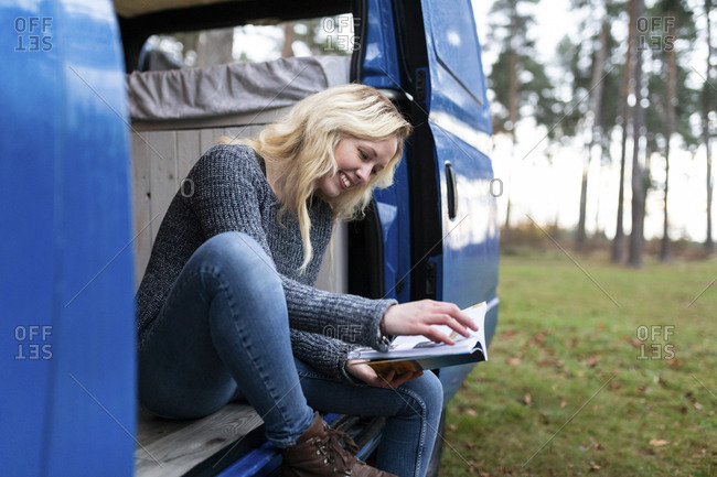 Happy woman reading book on door of camper van at Cannock Chase