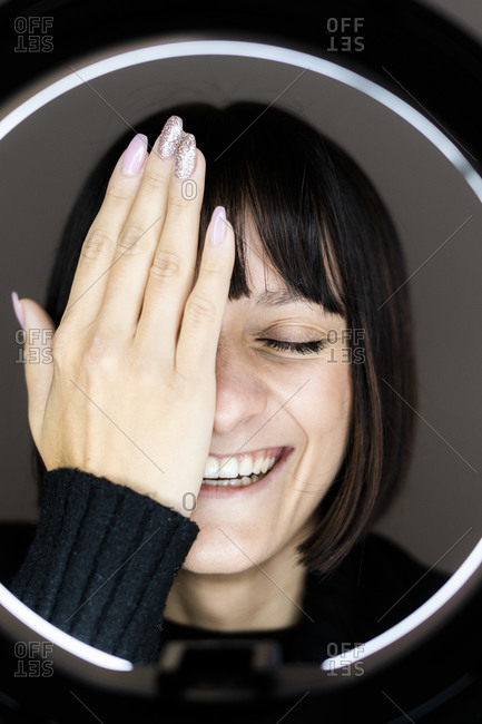 Happy young woman covering one eye with hand in front of light