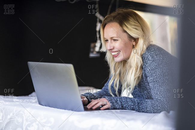 Happy woman working on laptop while lying on bed in camper van