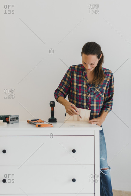 Mid adult woman  marking on wood while doing DIY work at home