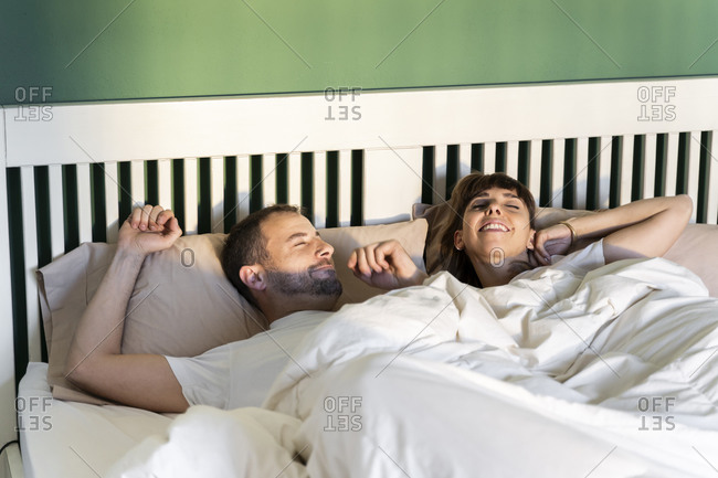 Man and woman waking up slowly while lying on bed at home