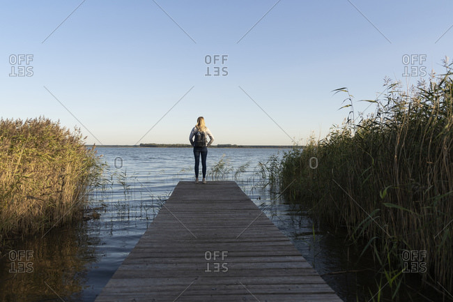 Tourist with backpack admiring sea while standing on jetty at Mecklenburg- Fischland-Darfl-Zingst- Germany