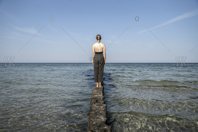 Woman looking at sea while standing on wooden groyne at Mecklenburg- Fischland-Darfl-Zingst- Germany