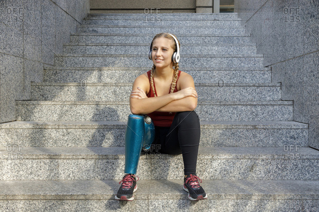 Smiling sportswoman with prosthetic leg wearing headphones sitting with arms crossed on staircase