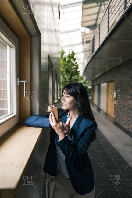 Businesswoman with smart phone looking through window while standing in corridor of office