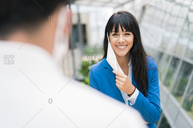 Smiling female entrepreneur looking at male colleague in office meeting while holding mask