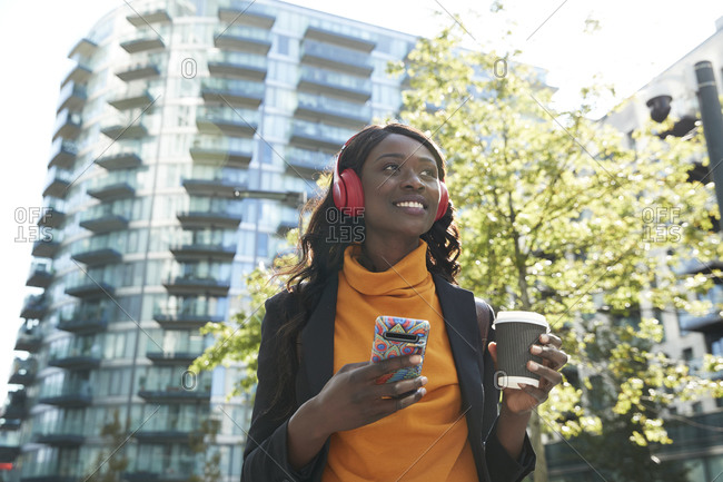 Businesswoman with disposable coffee cup day dreaming while listening music at office park