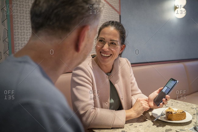 Businesswoman smiling while showing mobile phone to colleague while sitting at modern cafe