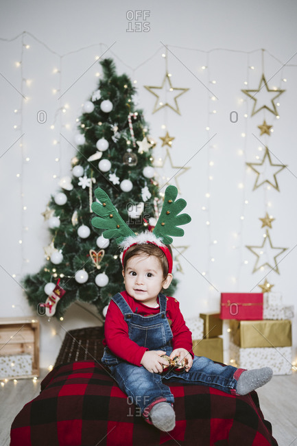 Cute boy wearing horned headband sitting against Christmas tree at home during Christmas