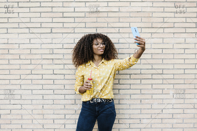 Young woman smiling while taking selfie through mobile phone standing against brick wall