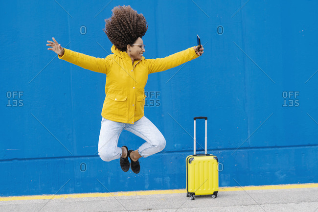 Young carefree woman jumping while taking selfie through mobile phone against blue wall
