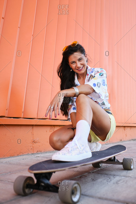 Portrait of beautiful girl crouching beside longboard in front of corrugated iron wall