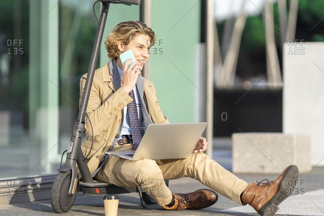 Businessman with laptop talking on mobile phone while sitting on electric push scooter