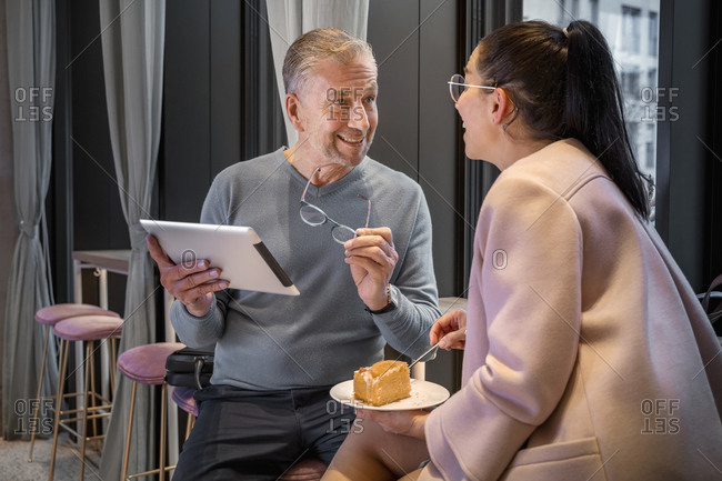 Businessman using digital tablet while sitting by colleague eating food at modern cafe