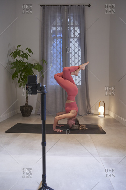 Female instructor doing yoga headstand while vlogging on mobile phone in exercise room