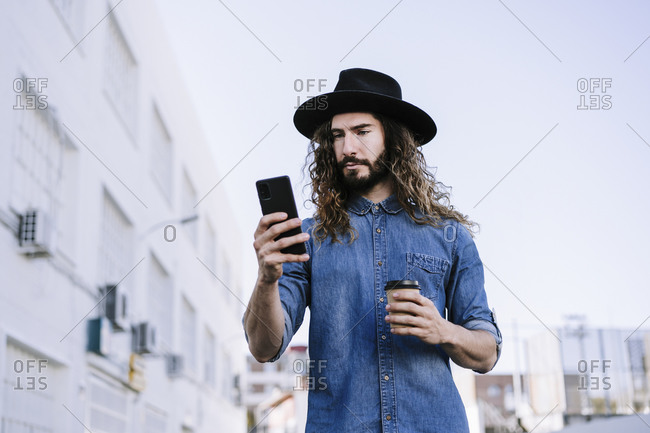 Fashionable young man with disposable coffee cup using mobile phone against clear sky