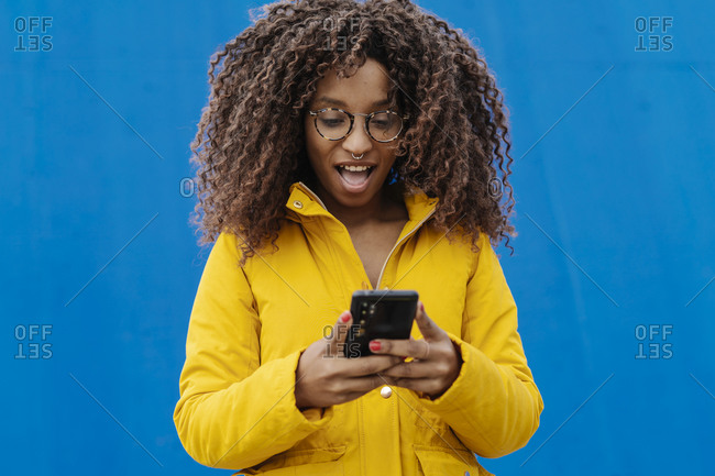 Surprised woman with mouth open using mobile phone while standing against blue wall