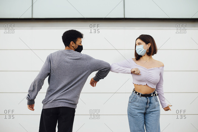 Young couple wearing face mask greeting with elbow bump while standing against wall