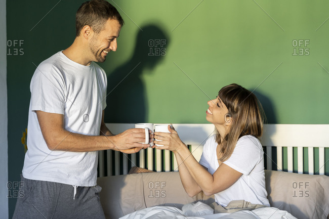 Smiling boyfriend and girlfriend toasting with coffee while sitting on bed at home
