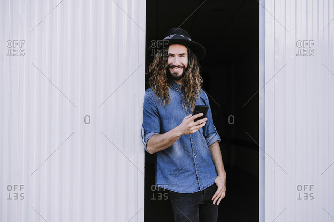 Happy stylish man leaning on corrugated wall while holding mobile phone in doorway
