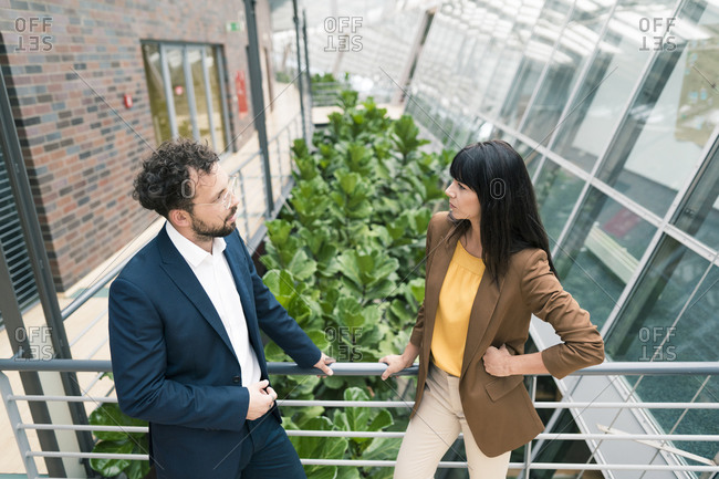 Businesswoman with hand on hip discussing with male colleague by railing at office