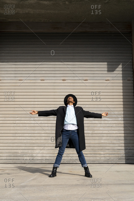 Young man in hat with arms outstretched looking up while standing against shutter