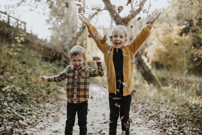 Happy sibling playing with dry fallen leaf while standing in forest during autumn