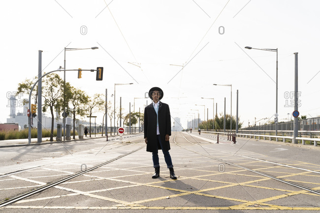 Young man wearing hat standing between railroad track on street during sunny day