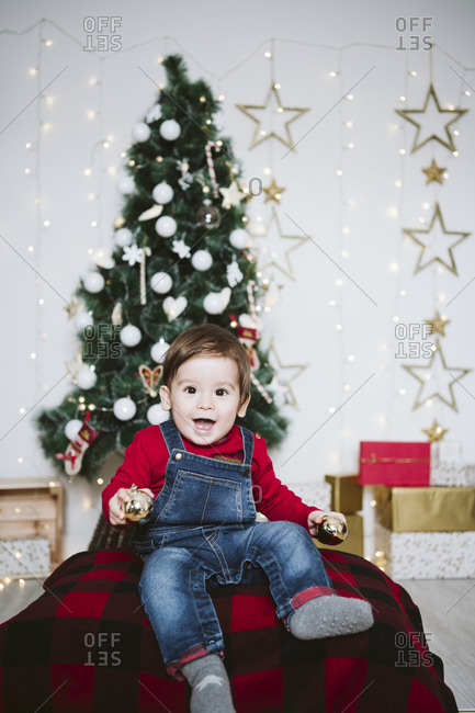 Cheerful baby boy with mouth open playing while sitting at home during Christmas