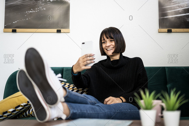 Happy woman capturing memories while leaning legs on coffee table in living room
