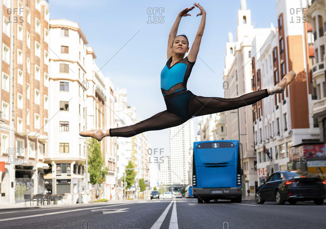 Female dancer with hand raised jumping with legs stretched while dancing in city