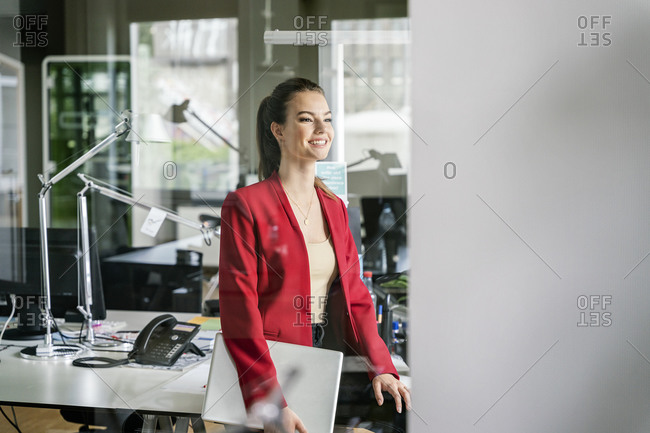 Happy businesswoman with laptop day dreaming while leaning on desk at work place
