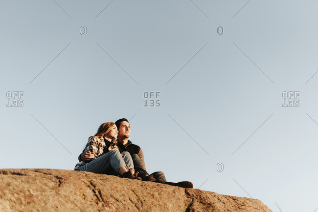Clear sky over young couple sitting together on rocky surface during autumn hike