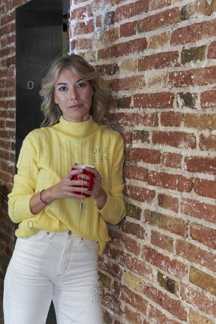Fashionable mature woman holding tea cup while leaning on brick wall in kitchen