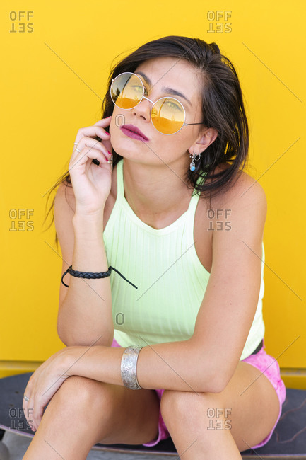 Portrait of beautiful girl sitting alone on longboard in front of yellow wall