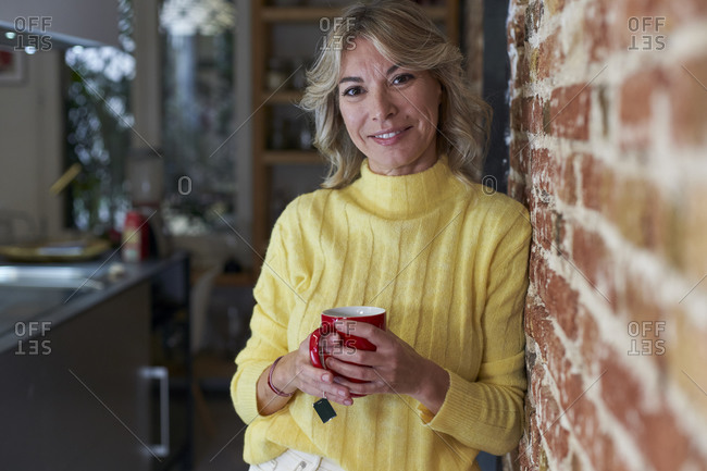 Smiling mature woman leaning on brick wall while holding tea cup in kitchen