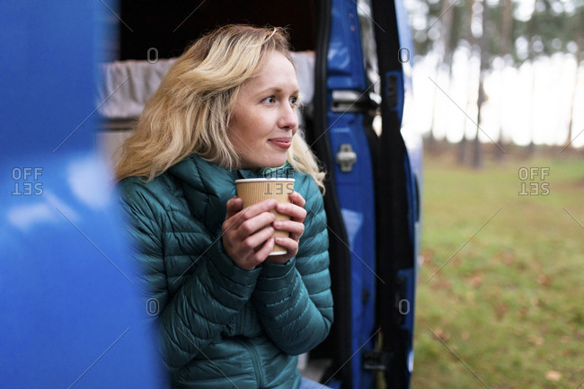 Thoughtful woman with disposable tea cup looking away at door of motor home
