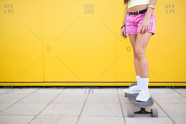 Low section of young woman standing on longboard in front of yellow wall
