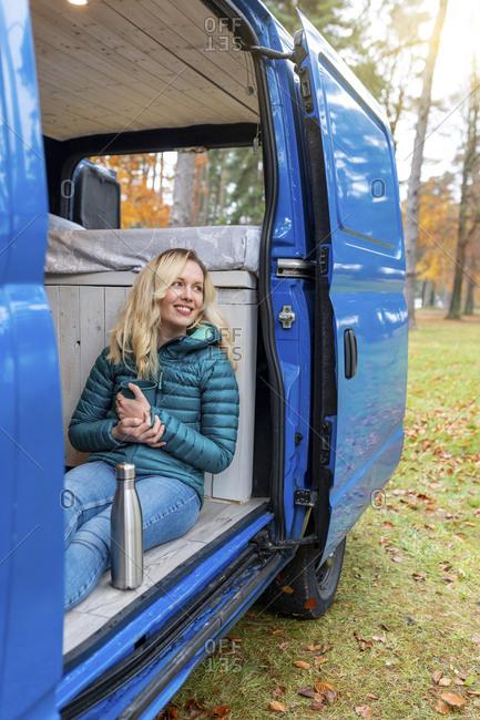 Happy woman looking away while holding tea cup at door of camper van