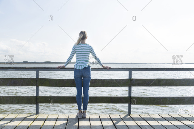 Woman looking at sea while standing on jetty against sky at Mecklenburg- Fischland-Darfl-Zingst- Germany