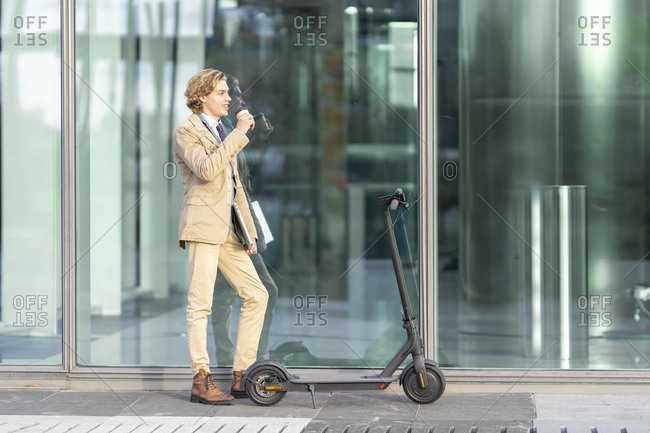 Businessman with laptop drinking coffee while standing by electric push scooter against glass wall