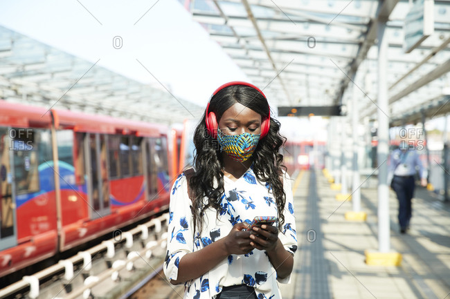 Businesswoman with face mask and headphones using mobile phone while standing at station platform