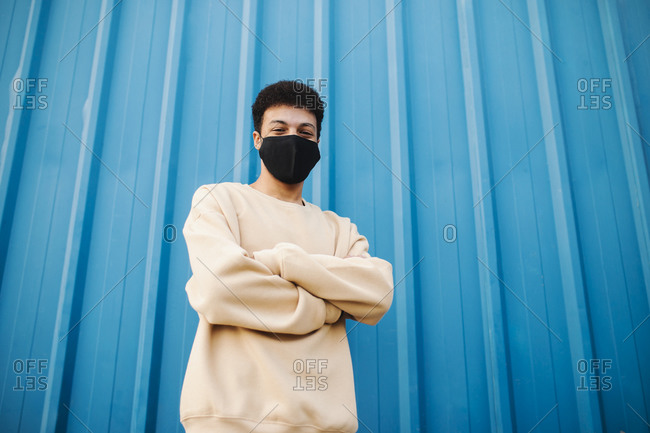 Man wearing protective face mask standing with arms crossed against blue wall during Covid-19